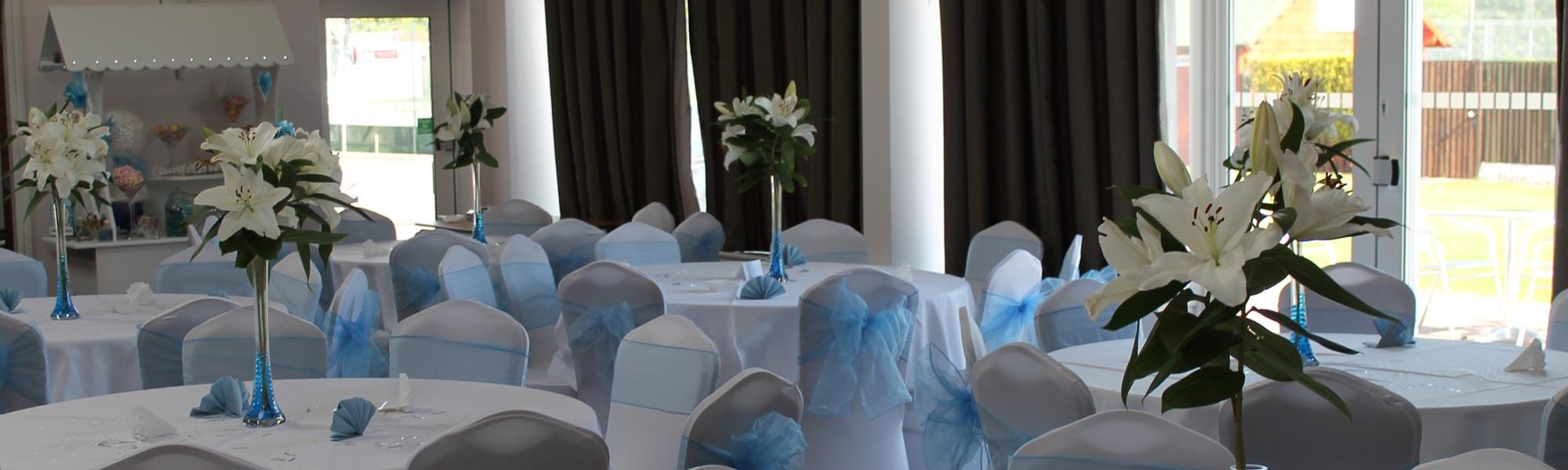Blue themed venue decoration with chair covers, sweet cart and centre pieces