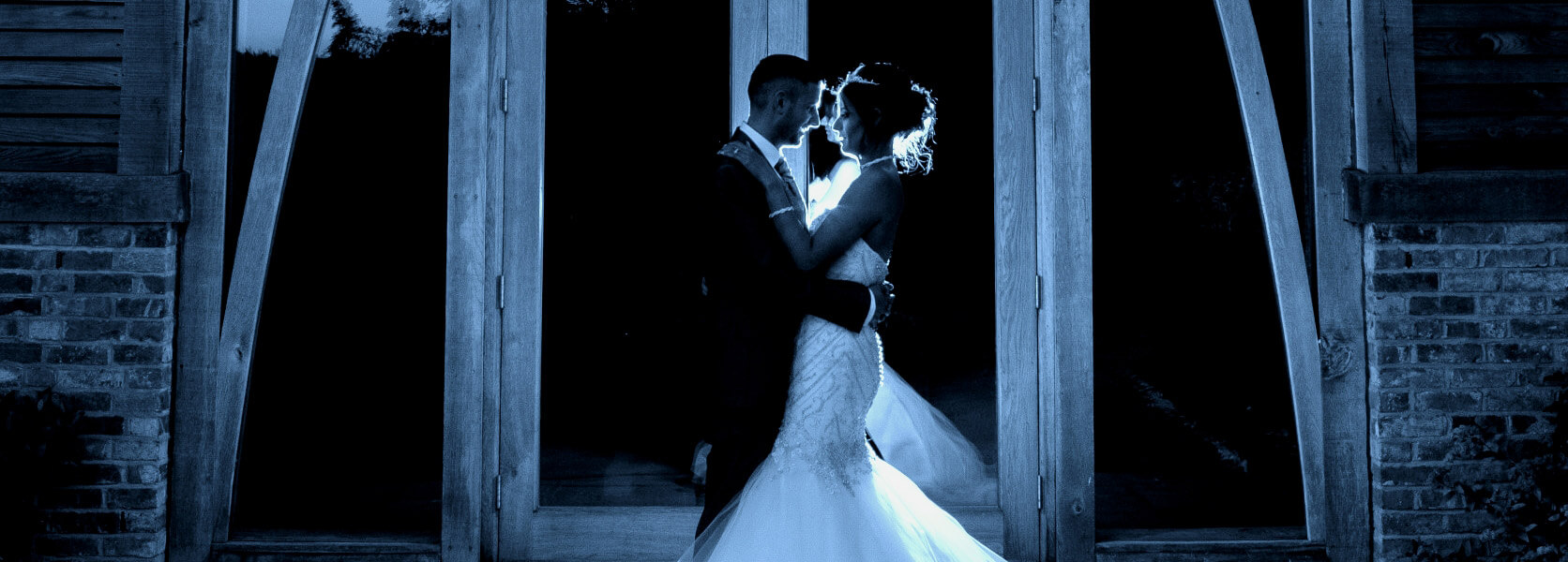 Gray scale image of couple embracing outside venue