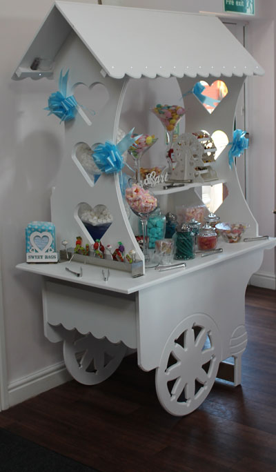 white wooden sweet cart accompanied with a variety of sweets