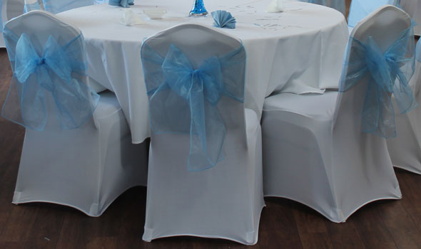 three chairs with white chair covers and blue bows