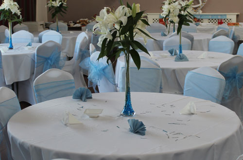 table with white table linen and origami napkins and centre piece